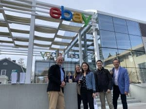 The five faculty members in front of the eBay sign