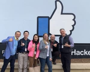 The CIC team in front of the Facebook sign